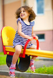 Den unga lyckliga flickan är svängande i lekplats Royaltyfri Foto