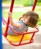 Den unga lyckliga flickan är svängande i lekplats Arkivbilder