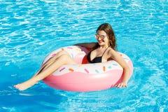 Den unga lyckliga flickan i bikini simmar i pölen med en rosa cirkel royaltyfri foto