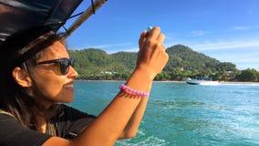 Den unga lyckliga flickan seglar på ett fartyg och tar bilder på den smarta telefonen krabi thailand lager videofilmer
