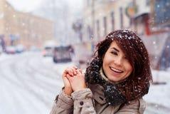 Den unga lyckliga flickan tycker om snö lyckligt nytt år Insnöat staden Arkivfoto