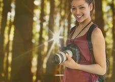 den unga lyckliga fotografen i skogen med signalljus och bokeh överlappar royaltyfri bild
