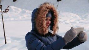 Den unga lyckliga härliga kvinnaappellvideoen som pratar i vinter, parkerar i staden i snöig dag med fallande snö Slapp fokus stock video