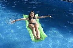 Den unga lyckliga härliga kvinnan, i att ligga för bikini och för solglasögon, kopplar av på flöteluftmadrass på simbassängen för Arkivbild