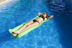 Den unga lyckliga härliga kvinnan, i att ligga för bikini och för solglasögon, kopplar av på flöteluftmadrass på simbassängen för Royaltyfria Bilder