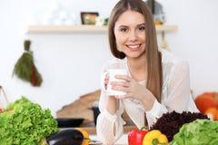 Den unga lyckliga kvinnan är den hållande vita koppen och att se kameran, medan sitta på trätabellen i kökamonen Royaltyfri Bild