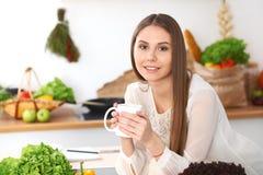 Den unga lyckliga kvinnan är den hållande vita koppen och att se kameran, medan sitta på trätabellen i kökamonen Royaltyfri Fotografi