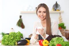 Den unga lyckliga kvinnan är den hållande vita koppen och att se kameran, medan sitta på trätabellen i kökamonen Arkivbilder