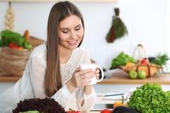 Den unga lyckliga kvinnan är den hållande vita koppen och att se kameran, medan sitta på trätabellen i köket bland royaltyfri foto