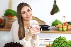 Den unga lyckliga kvinnan är den hållande vita koppen och att se kameran, medan sitta på trätabellen i köket bland royaltyfria foton
