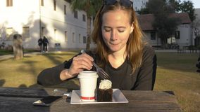 Den unga lyckliga kvinnan äter kakan som är utomhus- i, parkerar lager videofilmer