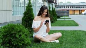 Den unga lyckliga kvinnan använder telefonen, medan sitta på gräsmattan nära hotelltrycken ett meddelande lager videofilmer