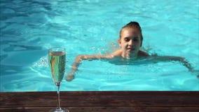 Den unga lyckliga kvinnan dricker champagne i en simbassäng lager videofilmer