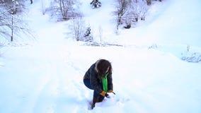 Den unga lyckliga kvinnan i ett snöig parkerar Kvinnan tar snön med henne händer och kastar den in i luften En kvinna är stock video