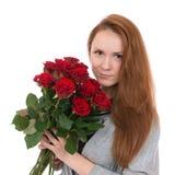 Den unga lyckliga kvinnan med buketten av röda rosor blommar Fotografering för Bildbyråer
