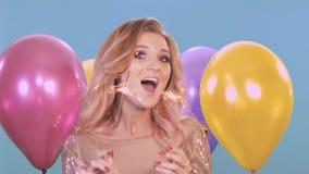 Den unga lyckliga kvinnan med tomtebloss firar och skrattar på blå bakgrund med ballonger lager videofilmer