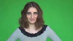 Den unga lyckliga kvinnan säger ja, genom att skaka hennes huvud posera mot en löstagbar chromatangentbakgrund stock video