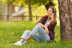 Den unga lyckliga kvinnan som talar på mobiltelefonsammanträde på gräs i sommarstad, parkerar Härlig modern flicka med en smartph Royaltyfri Foto
