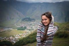 Den unga lyckliga kvinnan står på bakgrunden av en liten stad i dalen royaltyfri foto
