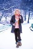 Den unga lyckliga kvinnan tycker om den insnöade vinterstaden parkerar utomhus- Fotografering för Bildbyråer