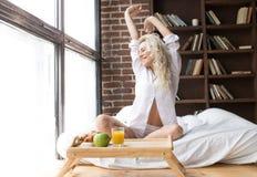 Den unga lyckliga kvinnan vaknar upp i säng med frukosten Royaltyfria Bilder