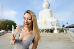 Den unga lyckliga kvinnavisningen tummar upp, den vita Buddhastatyn i Phuket i bakgrund royaltyfria bilder