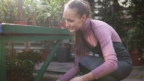 Den unga lyckliga le kvinnliga blomsterhandlaren med hästsvansen i förkläde ordnar krukor med växter på hyllan Lens signalljus stock video