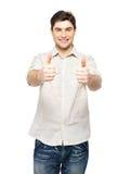 Den unga lyckliga manen med tum undertecknar upp i tillfälligt Arkivfoton