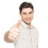 Den unga lyckliga manen med tum undertecknar upp i tillfälligt Arkivfoto