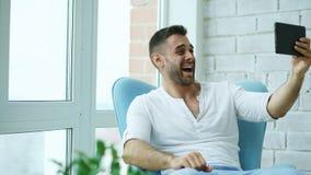 Den unga lyckliga mannen har online-video pratstund genom att använda digitalt minnestavladatorsammanträde på balkong i modern vi Royaltyfria Bilder