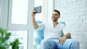 Den unga lyckliga mannen har online-video pratstund genom att använda digitalt minnestavladatorsammanträde på balkong i modern vi Royaltyfria Foton
