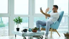 Den unga lyckliga mannen har online-video pratstund genom att använda digitalt minnestavladatorsammanträde på balkong i modern vi Arkivfoton