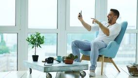 Den unga lyckliga mannen har online-video pratstund genom att använda digitalt minnestavladatorsammanträde på balkong i modern vi Fotografering för Bildbyråer