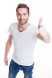 Den unga lyckliga mannen med tummar undertecknar upp in tillfälligt. arkivfoton