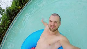 Den unga lyckliga mannen som kopplar av i vatten, parkerar simbassängen på den Rubber munkcirkeln GoPro Selfie thailand stock video