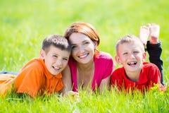 Den unga lyckliga modern med barn parkerar in Royaltyfri Bild