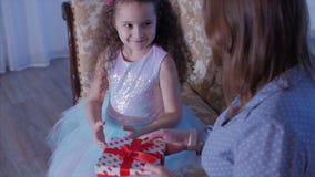 Den unga lyckliga modern med hennes öppna a gåvor för liten söt dotter, ser inåt och jublar i bakgrunden av stock video