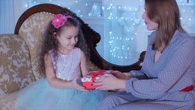 Den unga lyckliga modern med hennes öppna a gåvor för liten söt dotter, ser inåt och jublar i bakgrunden av lager videofilmer