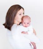 Den unga lyckliga modern som kysser hennes nyfött, behandla som ett barn arkivbilder