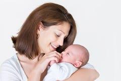 Den unga lyckliga modern som rymmer hennes nyfött, behandla som ett barn arkivbild