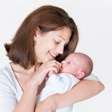 Den unga lyckliga modern som rymmer hennes nyfött, behandla som ett barn royaltyfri fotografi