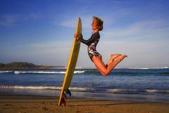Den unga lyckliga och attraktiva surfareflickan som högt hoppar i det hållande bränningbrädet för luft, innan han surfar på den h fotografering för bildbyråer