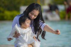 Den unga lyckliga och gulliga asiatiska japanska kvinnan som spelar med dottern, behandla som ett barn flickan på för semesterort royaltyfri bild