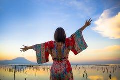 Den unga lyckliga och härliga koreanska kvinnan i traditionell asiatisk klänning på soluppgånghavslandskapet som bort ser med arm royaltyfria foton