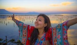Den unga lyckliga och härliga koreanska kvinnan i traditionell asiatisk klänning på soluppgånghavslandskapet som bort ser med arm arkivfoton