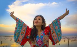 Den unga lyckliga och härliga koreanska kvinnan i traditionell asiatisk klänning på soluppgånghavslandskapet som bort ser med arm royaltyfria bilder
