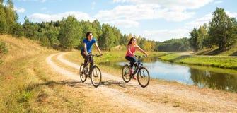 Den unga lyckliga parridningen cyklar förbi floden Royaltyfri Bild