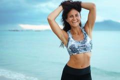 Den unga lyckliga stilfulla sportkvinnan har gyckel på havskust royaltyfri fotografi