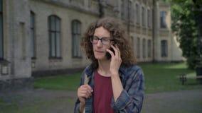 Den unga lyckliga studenten med lockigt hår som går till högskolan och talar på telefonen som in går, parkerar nära universitetet lager videofilmer