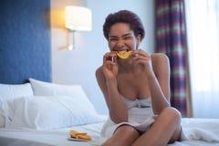 Den unga lyckliga svarta kvinnan sitter, i en säng och att äta den orange skivan Arkivfoto